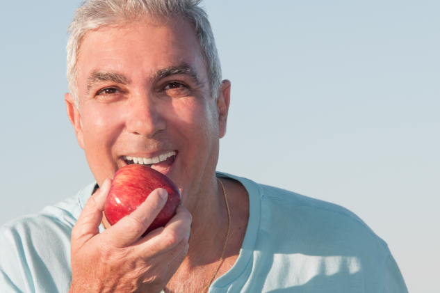 Man with dental implants biting into an apple near North Phoenix AZ
