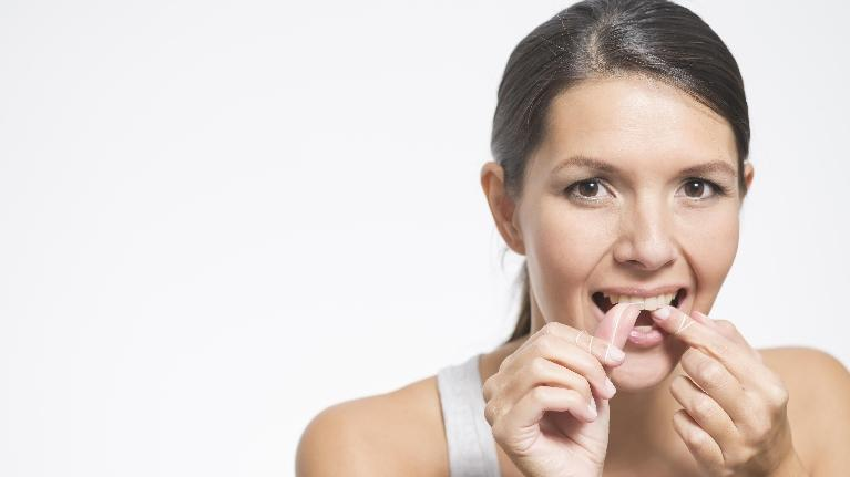 woman flossing her teeth to prevent gum disease