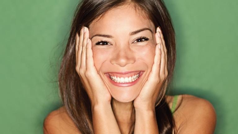 Woman smiling & holding her face | Best Dentist in Phoenix AZ